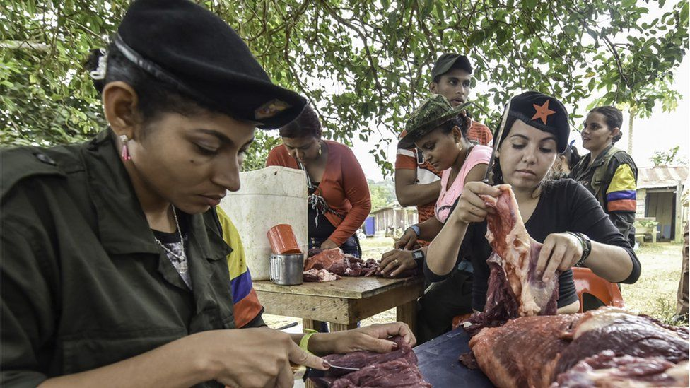 Members of the Revolutionary Armed Forces of Colombia (FARC) prepare meat at a camp in the Colombian mountains on February 18, 2016.
