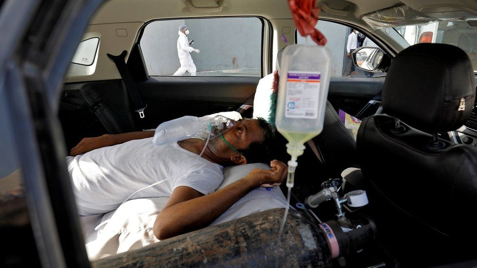 A patient with breathing problems lies inside a car while waiting to enter a Covid hospital for treatment in Ahmedabad, India