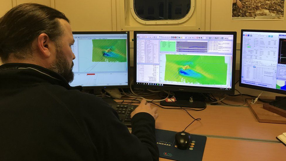 Technician Ben Powell viewing sonar images on board the survey vessel