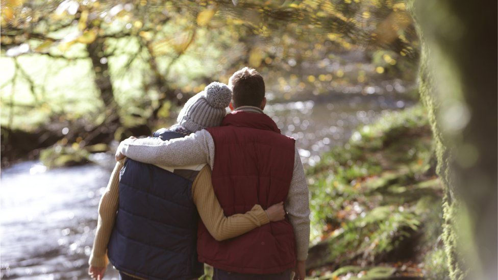 Couple walking by a river