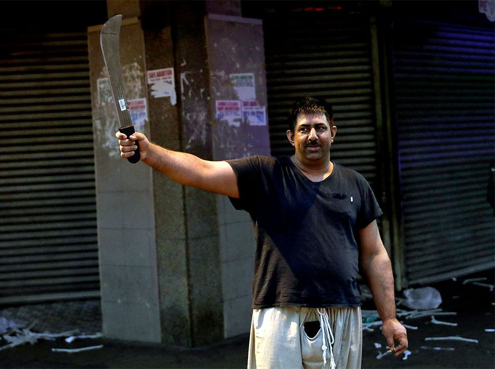 A shop owner holds a machete after staying up all night to protect his business during widespread looting and protests in Durban, South Africa, on 12 July 2021