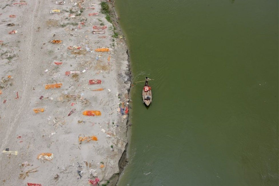 A man rows his boat past shallow sand graves of people, some of which are suspected to have died from the coronavirus disease (COVID-19), on the banks of the river Ganges in Phaphamau on the outskirts of Prayagraj, India, May 21, 2021