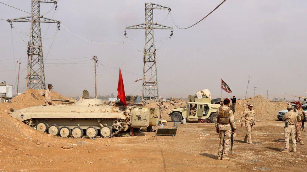 Iraqi forces stand guard near the al-Qaim border crossing between Syria and Iraq on 8 November 2017