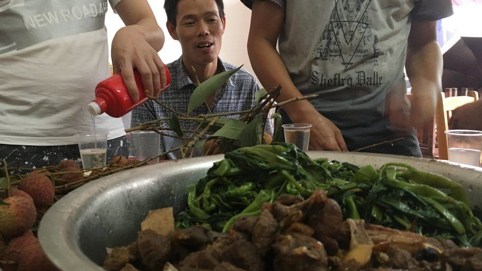 A man sitting in front of a stew at the Yulin festival