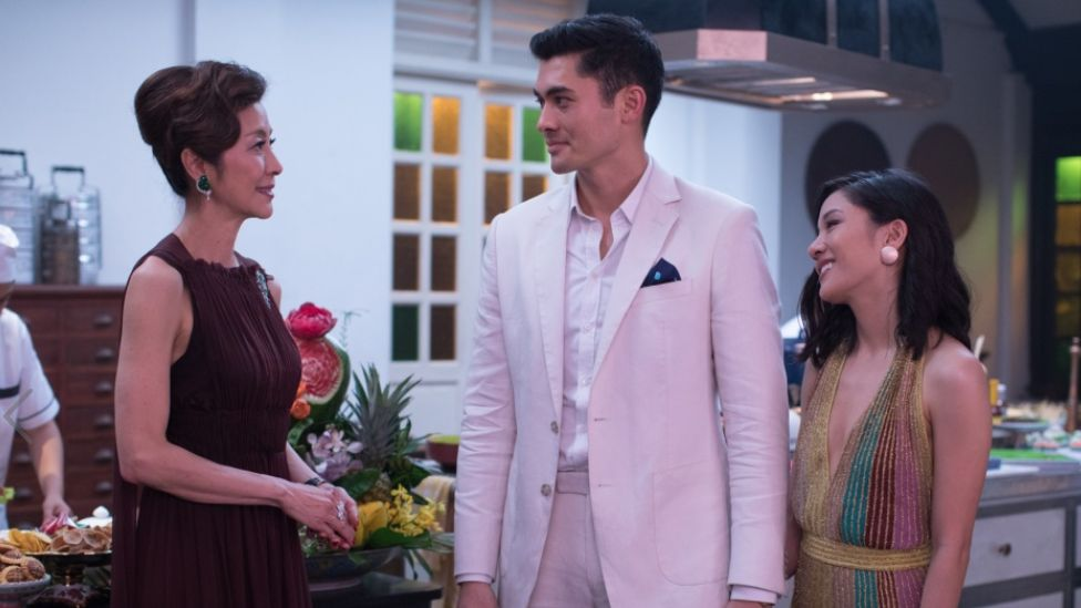 Movie still from Crazy Rich Asians showing Michelle Yeoh, Henry Golding and Constance Wu smiling at one another