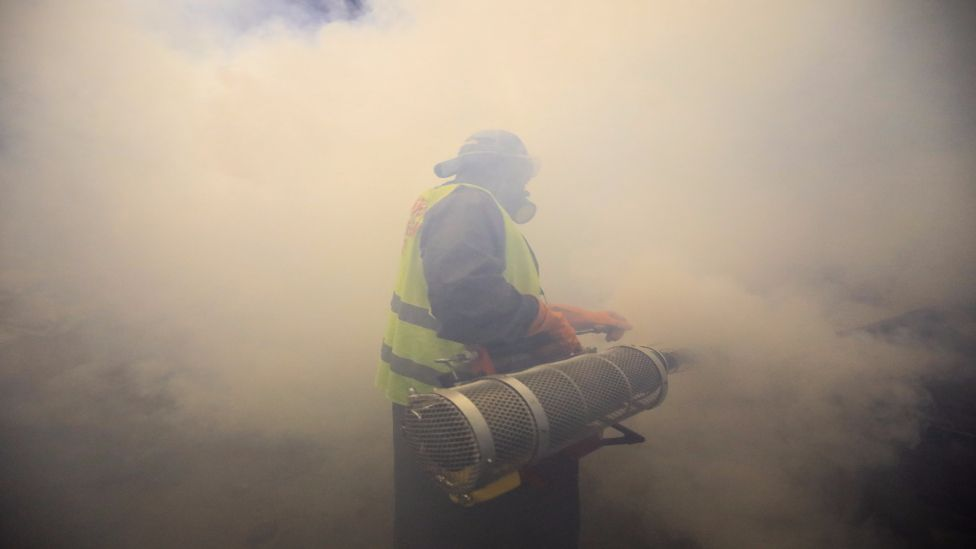 A member of the Sonko Rescue Team, an NGO founded by Nairobi Governor Mike Sonko, uses a smoke machine to spray streets