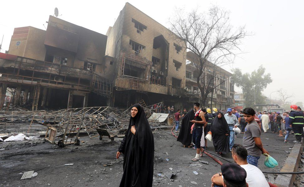 """Iraqis, including firefighters, gather at the site of a suicide car bombing claimed by the Islamic State group on July 3, 2016 in Baghdad""""s central Karrada district."""