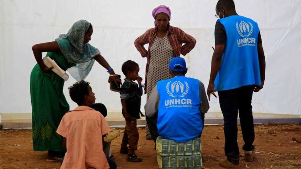 Humanitarian workers from UNHCR talk to Ethiopian refugees