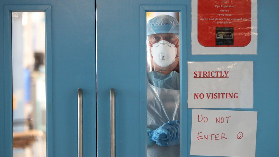 An infection control nurse looks out from a Covid-19 recovery ward at Craigavon Area Hospital in May 2020
