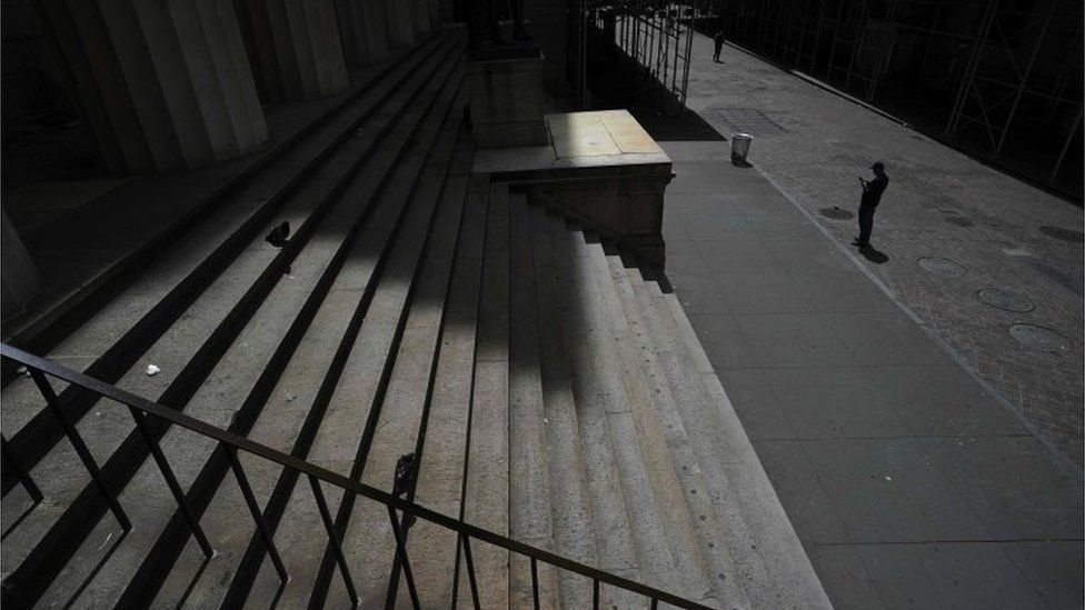 A person on the empty streets in front of the New York Stock Exchange