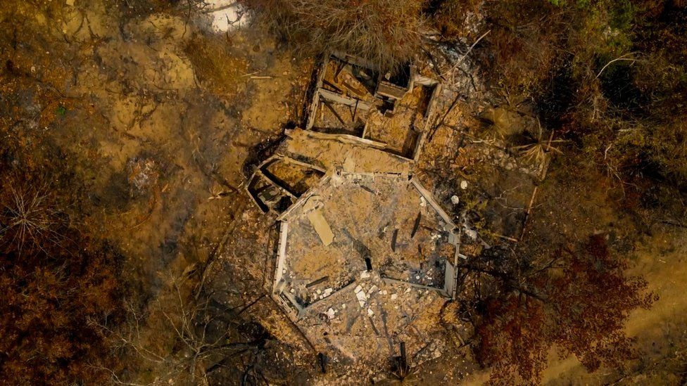 An aerial view of a burnt out building in the middle of a burnt forest