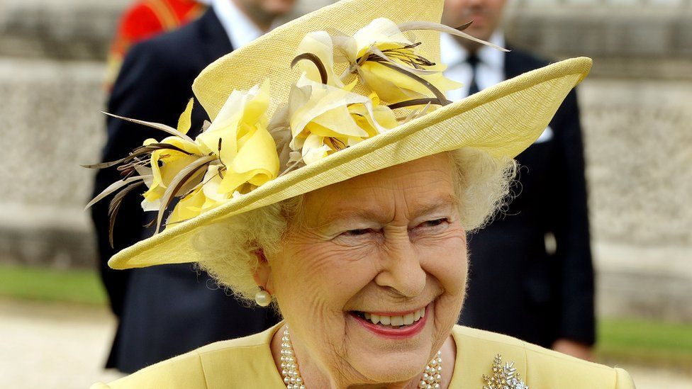 The Queen wearing a yellow floral hat