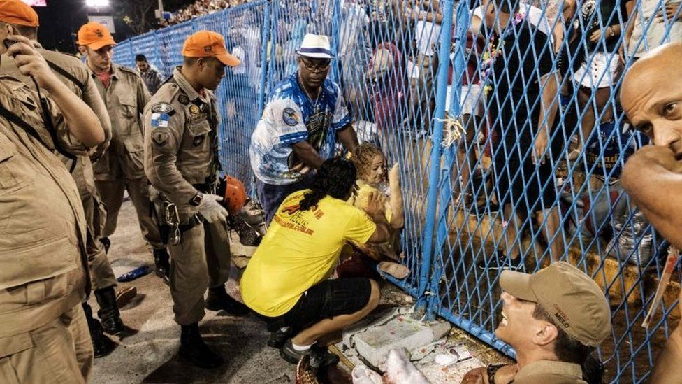 A woman in assisted by firefighters after being run over by a float of the Paraiso do Tuiuti samba school at the entrance of the Sambadrome during the first night of Rio's Carnival, in Rio de Janeiro, Brazil, on February 26, 2017.