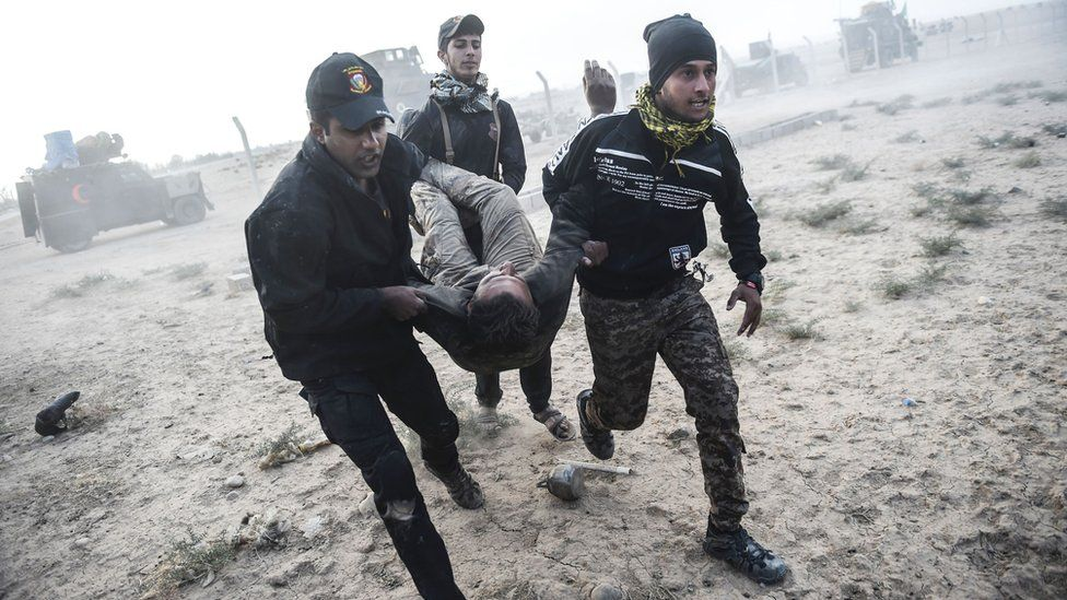 Iraqi Counter Terrorism Service (CTS) personnel carry an injured comrade during clashes with Islamic State (IS) on the eastern edges of Mosul, 31 October 2016