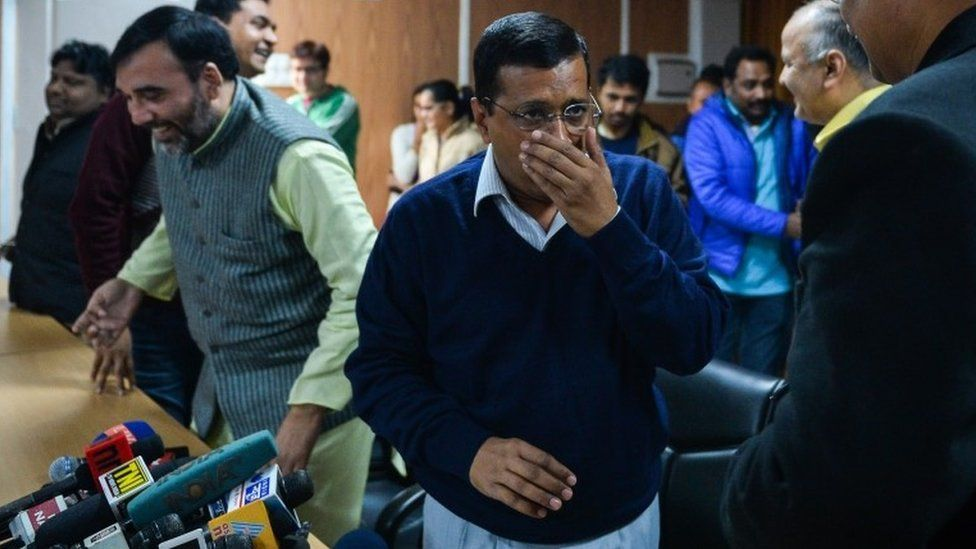 Delhi Chief Minister Arvind Kejriwal (C) coughs ahead of addressing the media at a press conference in New Delhi on December 24, 2015