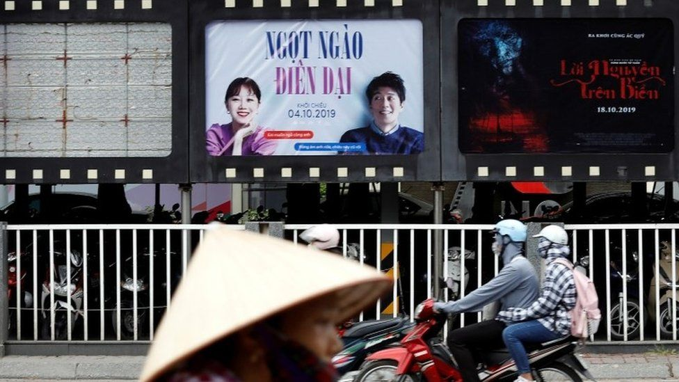 "Bikers go past an empty space where a promotional poster for ""Abominable"" stood before being taken down at a cinema in Hanoi"