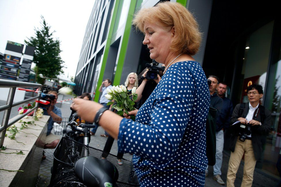 A woman lights a candle outside the Olympia shopping mall in Munich, 23 July