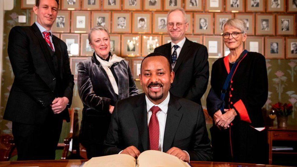 Ethiopia's Prime Minister and this year's Nobel Peace Prize Laureate Abiy Ahmed Ali (C) signs the Nobel Protocol at his arrival in Oslo