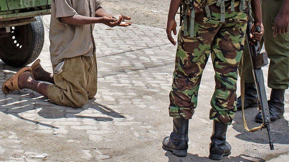 A man on his knees during a raid by the security services in Mombasa, Kenya