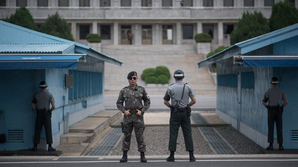 """In a photo taken on August 2, 2017 South Korean soldiers stand guard before North Korea""""s Panmon Hall (rear C) and the military demarcation line separating North and South Korea, at Panmunjom, in the Joint Security Area (JSA) of the Demilitarized Zone (DMZ)."""