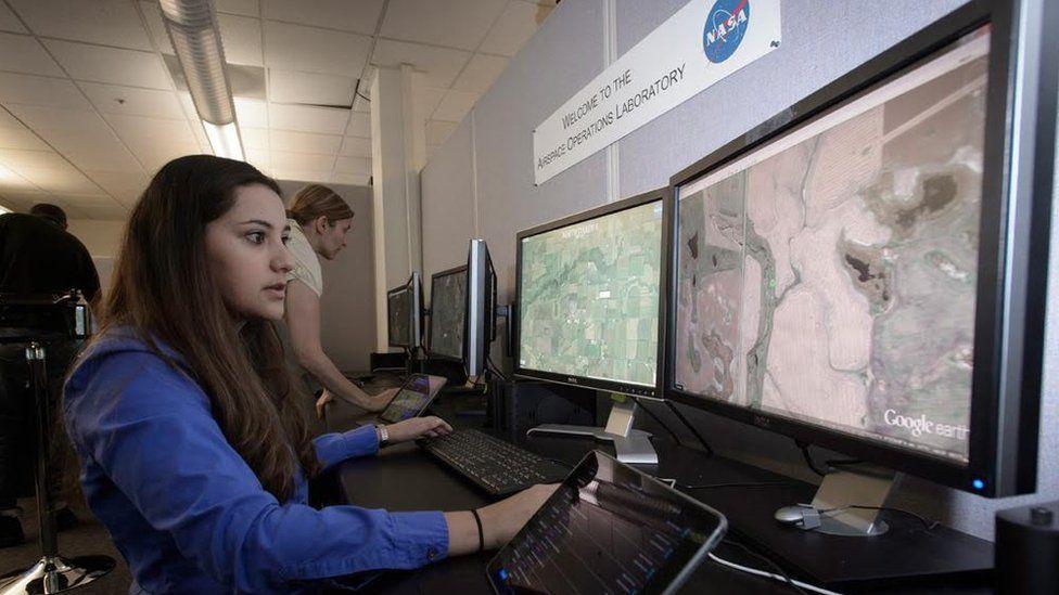 Woman monitoring big computer screens