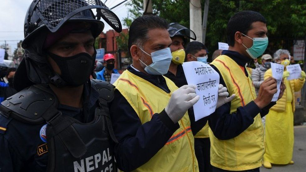 """Human rights activists hold placards during a protest against India""""s newly inaugurated link road to the Chinese border, near Indian embassy in Kathmandu on May 12, 2020."""