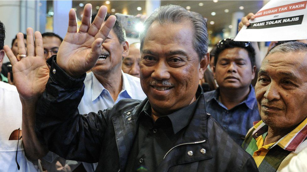 Former Malaysian Deputy Prime Minister Muhyiddin Yassin waves to photographers upon his arrival at Kuala Lumpur International Airport on 1 March