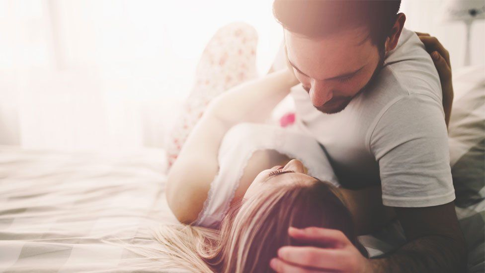 A stock image of a couple lying together in bed