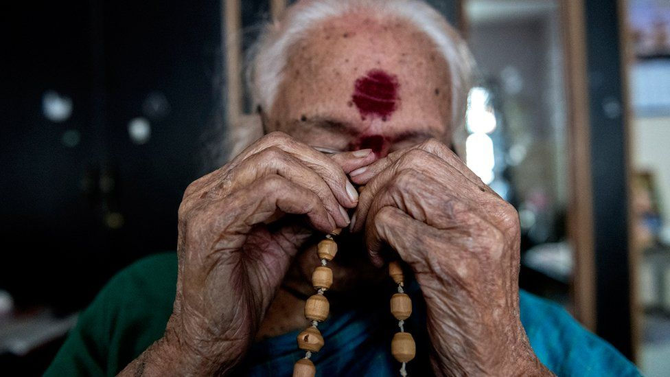 Ms Susheela holds holy beads in her hands as she prays