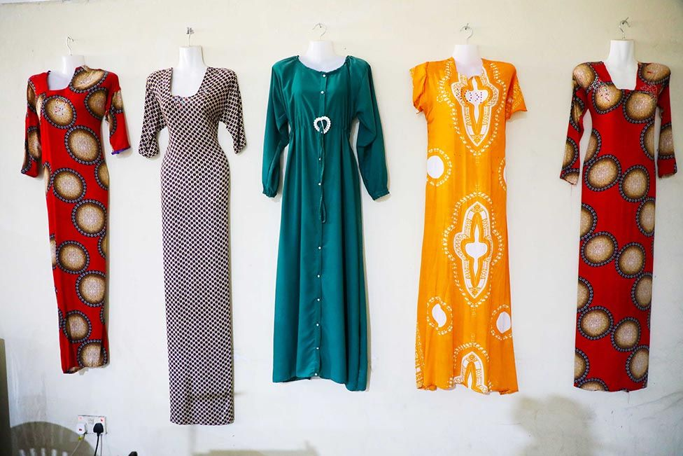 Dresses sewn by former militants training as tailors hang on a wall