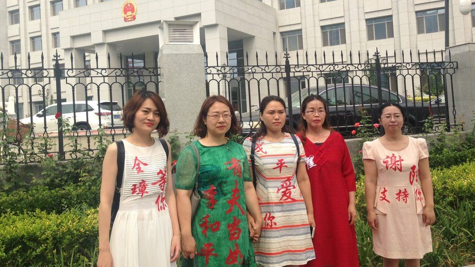 """Wives protesting outside the top prosecutor's office. The characters on the dresses read (from left to right): """"Quanzhang, I am waiting for you"""", """"If you want to marry a husband, Li Heping is the one"""", """"Geping, love you"""", """"Zhai Yanmin"""" (Zhai Yanmin is one of the detained activists) and """"Xie Yang, I support you"""""""