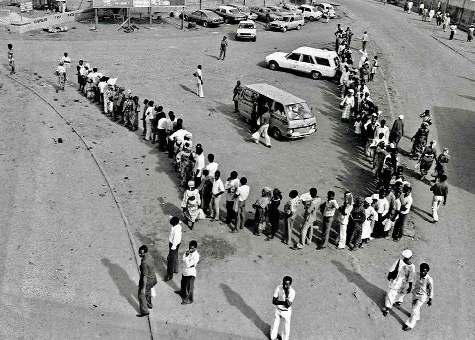 "A photo by Sunmi Smart-Cole entitled: ""Why... No Buses"" - 1984, showing Nigerians waiting in a line for a bus"
