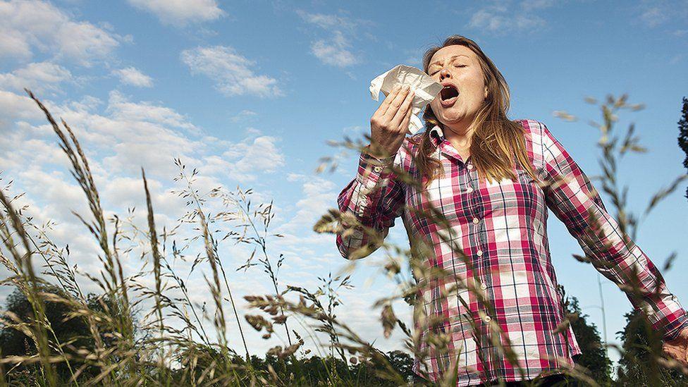 Woman sneezing in a field