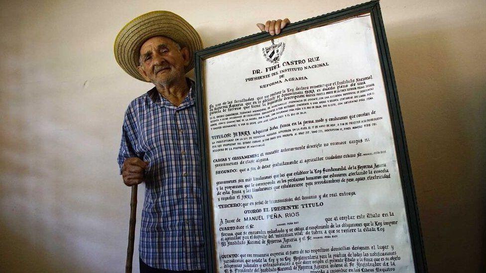 马诺洛拍摄了一张他收到的土地文件复本的照片,而57年后他的土地又归还了国家。