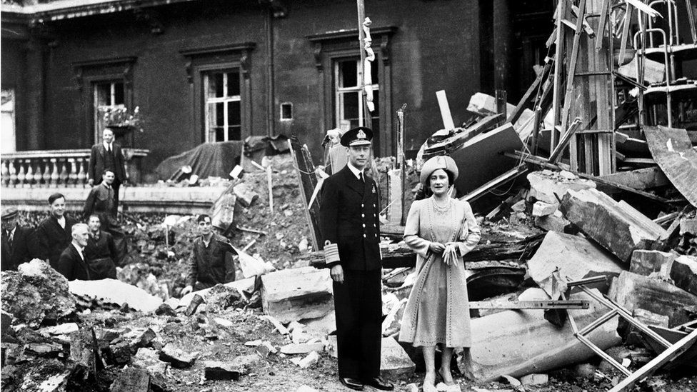 King George and the Queen Mother pictured next to a bomb-damaged Buckingham Palace in 1940