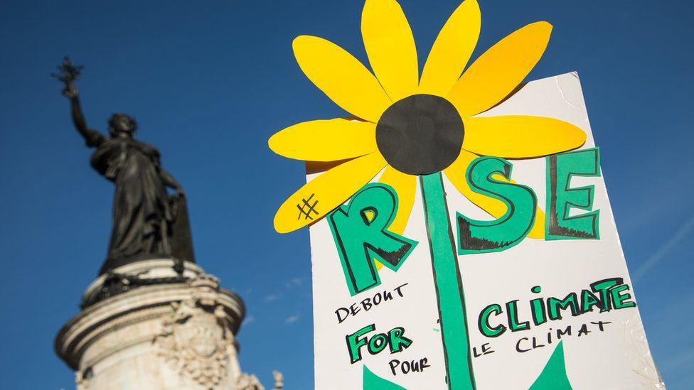 """A hand-drawn sunflower on a """"Rise for the Climate"""" poster during the """"March for the climate"""", in Republic Square, Paris, France on 8 September 2018"""