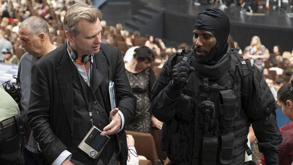 Tenet is directed by Christopher Nolan (left) and stars John David Washington