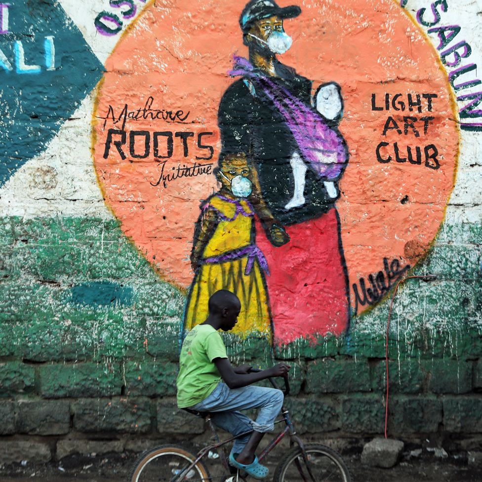 A boy on a bicycle riding past a mural of a woman and child in a face mask in Mathare slum, Nairobi, Kenya - Wednesday 8 April 2020