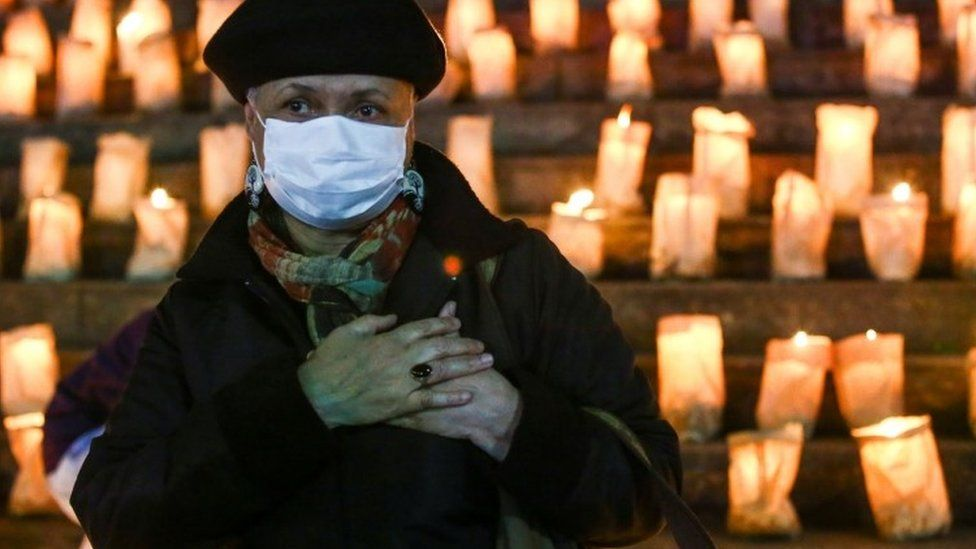 A woman clutches her heart at a candlelit memorial in Brazil