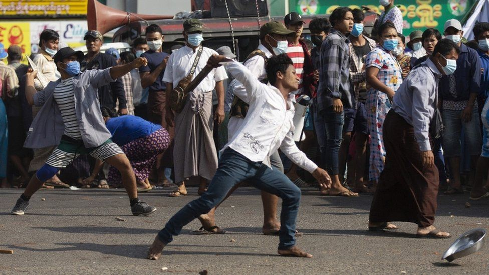 Pro-military supporters hurl stones at residents near the central railway station in Yangon, Myanmar