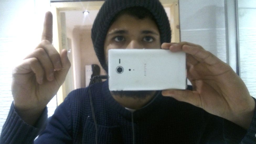 Aqib Imran taking a selfie and holding up one finger, in the style of an ISIS supporter