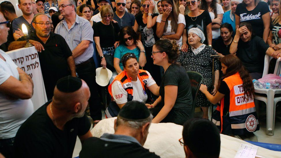 Relatives and friends mourn beside the body of Yotam Ovadia at a Jerusalem cemetery on 27 July 2018
