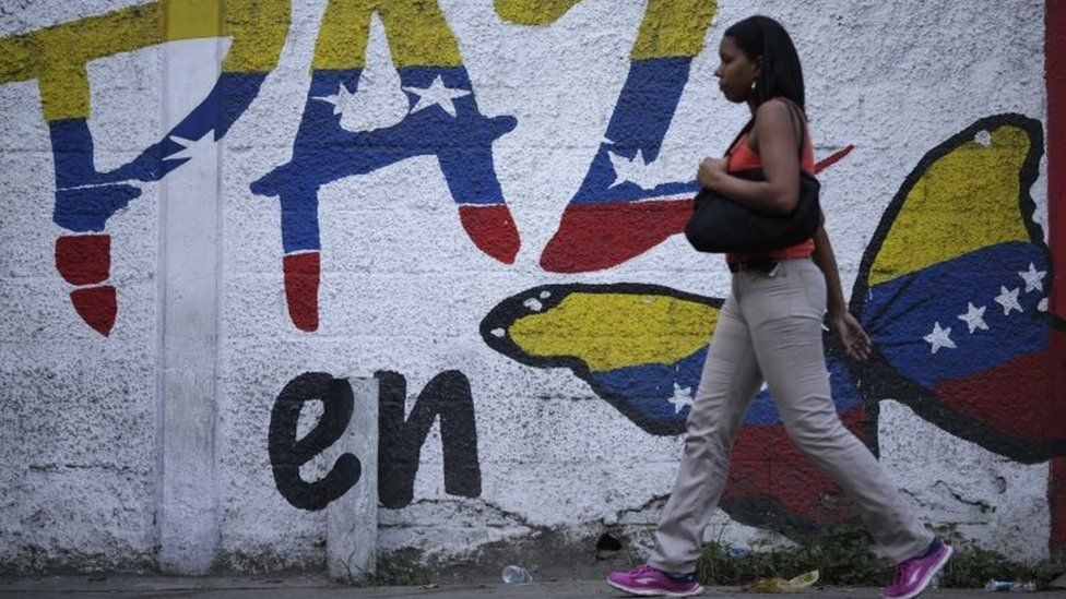 A woman walks past a mural calling for peace in Venezuela during the Constituent Assembly election in Caracas, Venezuela July 30, 2017.