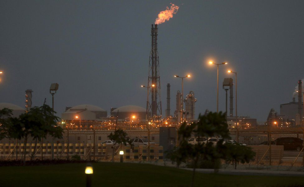 Lights illuminate a phosphate processing plant as a flame burns from a chimney in Saudi Arabia