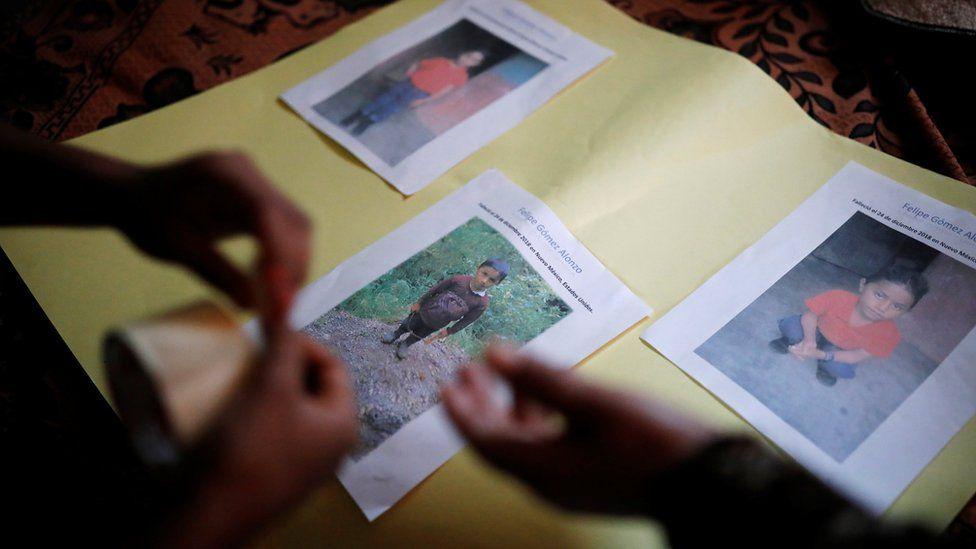 The family of Felipe Alonzo-Gomez arranges photos of the dead boy in the village of Yalambojoch, Guatemala, 27 December