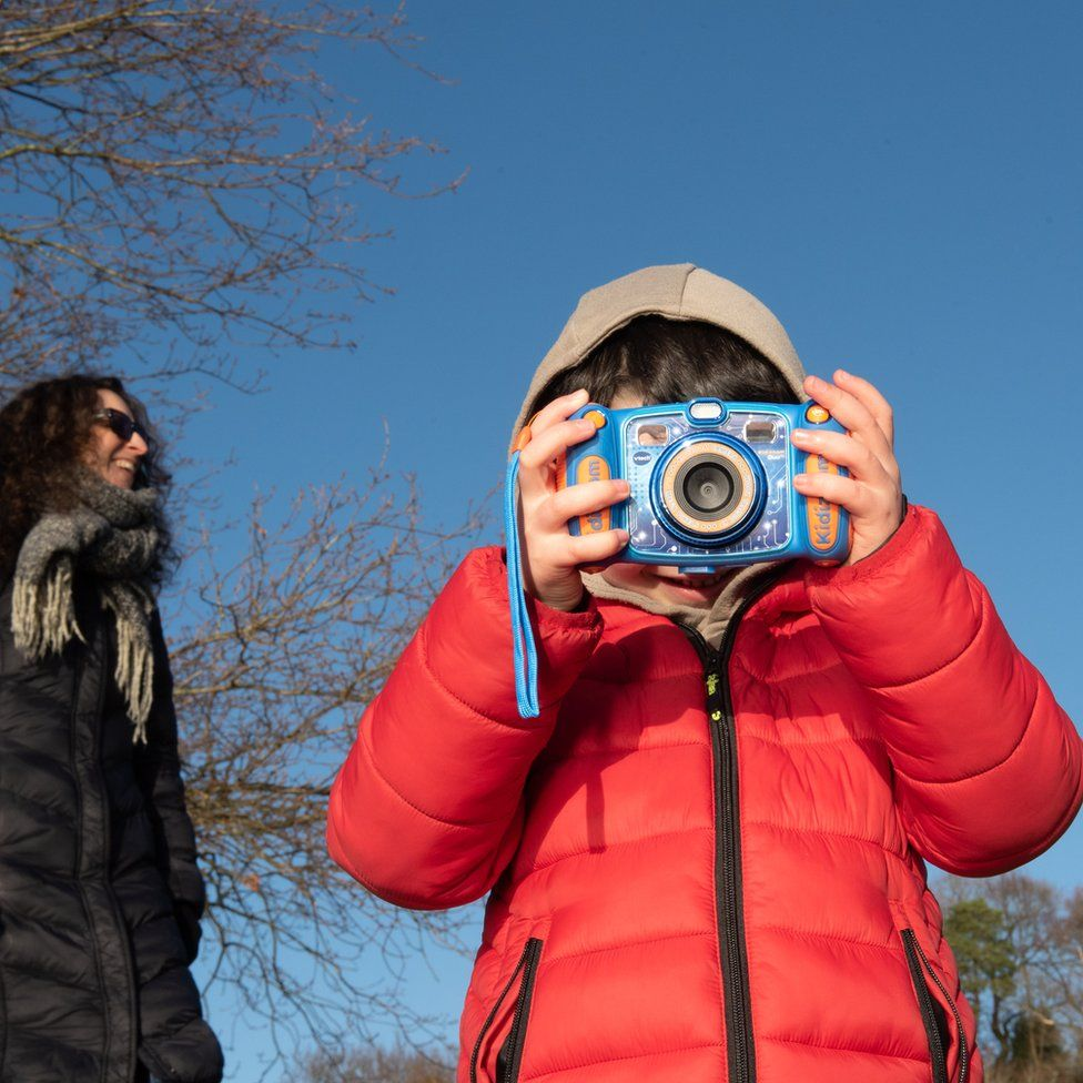 Katy and Ramona - a woman stands near a child who poses with a camera