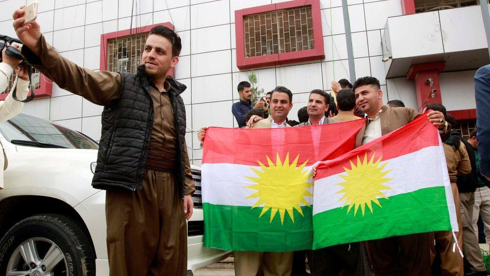Kurds take pictures with Kurdish flags at the Kirkuk Governorate Council building in Kirkuk, Iraq (6 April 2017)