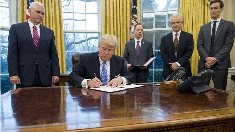 US President Donald Trump signs an executive order ending the US participation in the Trans-Pacific Partnership, alongside former White House Chief of Staff Reince Priebus, US Vice President Mike Pence and Senior Advisor Jared Kushner in the Oval Office of the White House