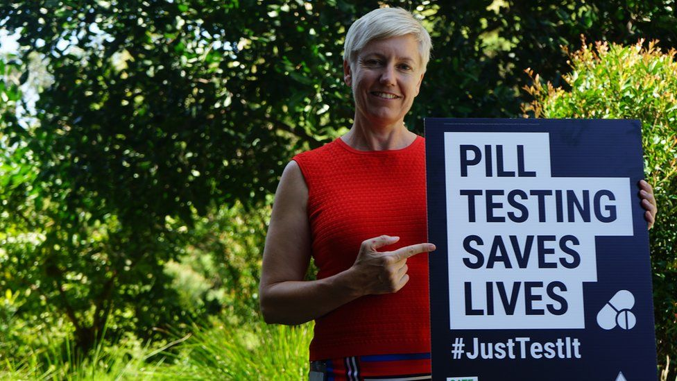 """Cate Faehrmann holds a sign saying: """"Pill testing saves lives""""."""