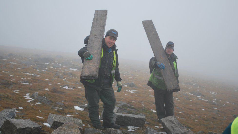 Andrew Rooney and Martin Stevenson carrying scaffolding planks down from the summit of Slieve Donard